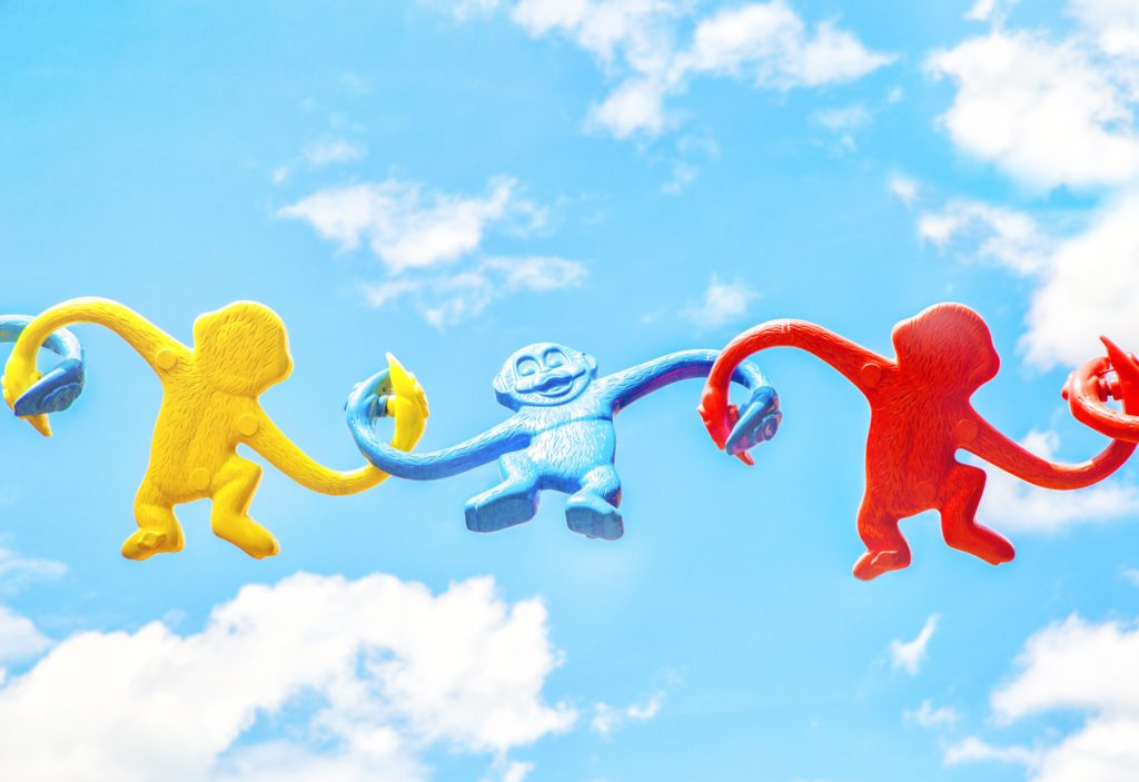 picture of toy monkeys in a chain of support with the background of a blue sky