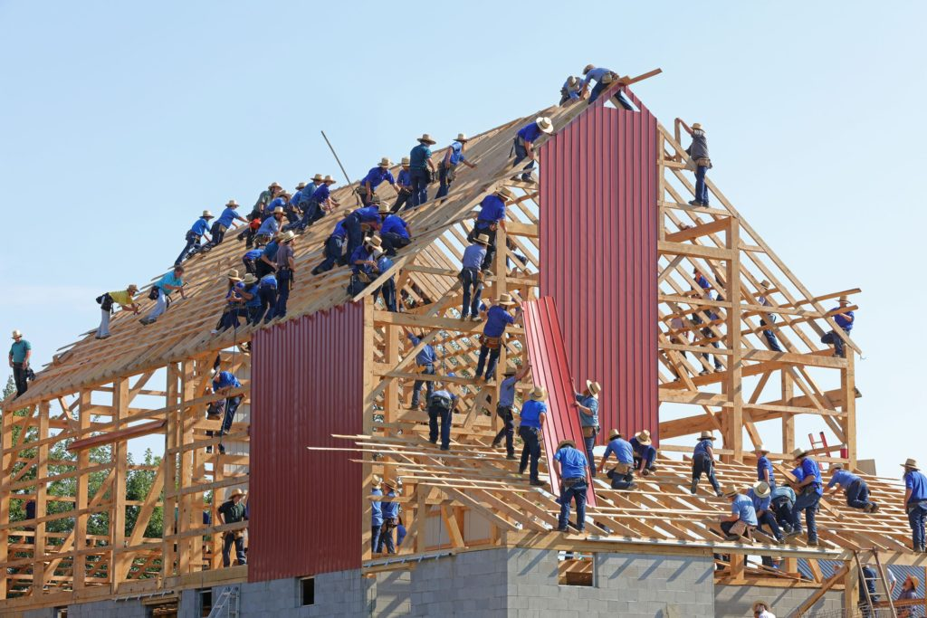 multiple people building a house together