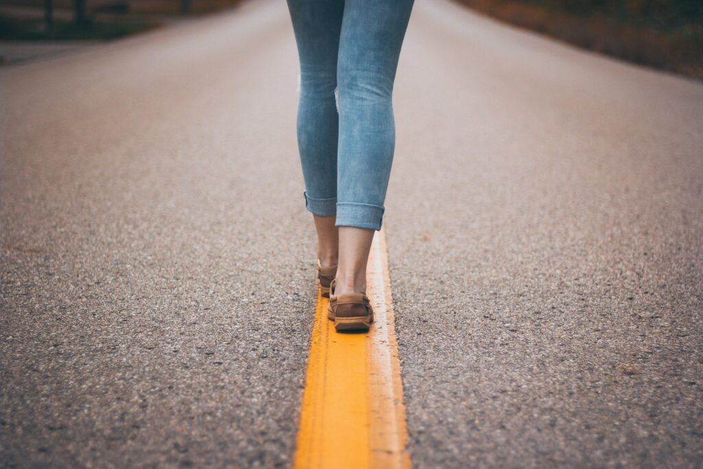 woman walking along a line in the road